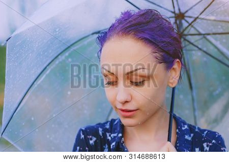 Portrait Of Sad Wet Woman Under Summer Rain With Umbrella. Bad Stormy Rainy Weather Concept. Violet