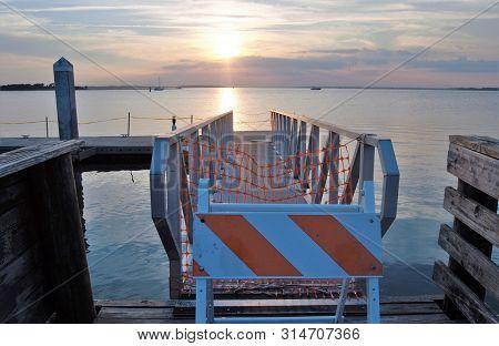 Orange And White Caution Sign On Pier Against Sunset Horizon