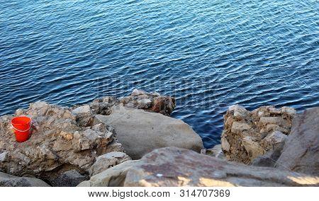 Orange Toy Bucket On Rocks By Water