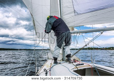 The Skipper Sets Sail On A Small Sports Yacht At Sea.