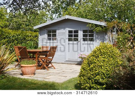 Shed With Terrace And Wooden Garden Furniture In A Garden During Spring