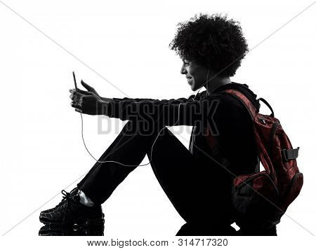 one mixed race african young teenager girl woman using telephone in studio shadow silhouette isolated on white background