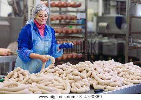 Butchers Processing Sausages At A Meat Factory.