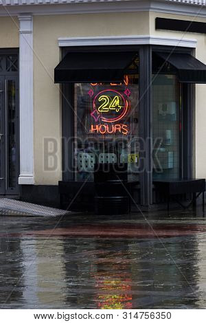 Open 24 Hours Neon Sign On A Restaurant Window With Italian Awnings. Summer Rainy Evening. Streetfoo