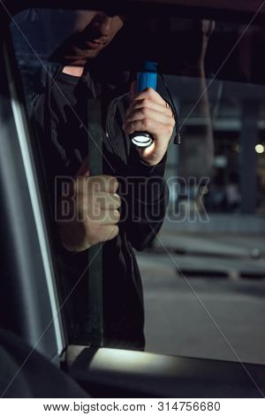 Cropped View Of Thief Intruding Car With Flashlight And Crowbar