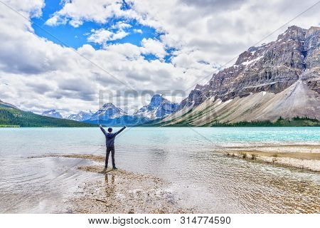 Man With Arms Raised In Front Of Bow Lake In Banff National Park, With Crowfoot Mountain And Crowfoo