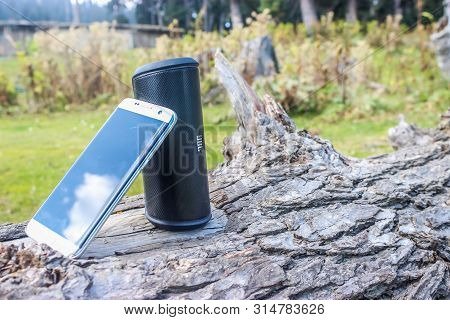 Kashmir, India: Dated: July 31, 2019- A Smartphone And A Jbl Bluetooth Portable Speaker Kept On A Lo
