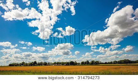 Sunny Spring Day In American Countryside. Rural Scene, Farmland With Trees And Buildings, Blue Sky W