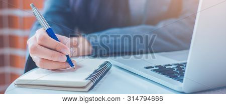 Woman Hand Is Writing On A Notepad With A Pen And Have A Laptop Computer On The Desk In The Office.w