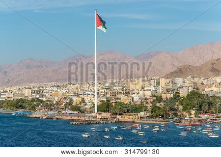 Aqaba, Jordan - November 6, 2017: Cityscape Of Aqaba And Flag Of Jordan Waving Over The City.  Arab