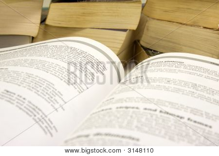 Open Book With Stack Of Books.