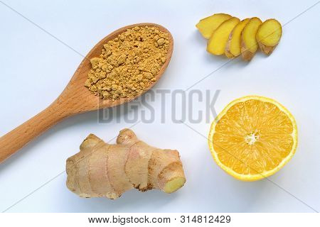 Yellow Lemon, Slices Of Ginger, Ginger Root And A Wooden Spoon With Ground Ginger On White Backgroun