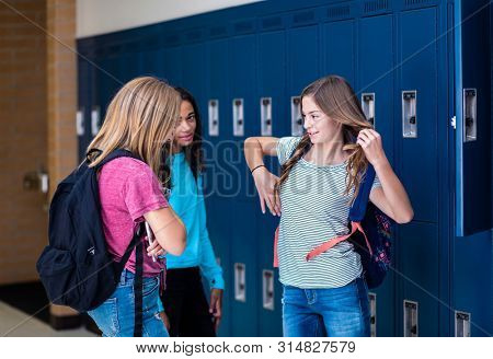 Candid photo of Three Junior High school Students talking together in a school hallway. Diverse Female school girls smiling and having fun together during a break at school