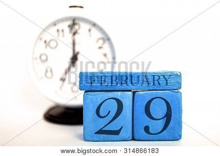February 29th. Day 29 Of Month, Handmade Wood Calendar And Alarm Clock On Blue Color. Winter Month,