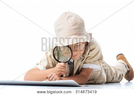 Focused Explorer Child In Hat And Glasses Looking At Placard Through Magnifying Glass On White