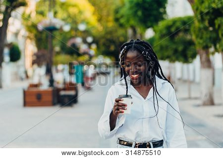 Portrait Of A Smiling Young African American Girl With Pigtails With Coffee Walking In The Street On