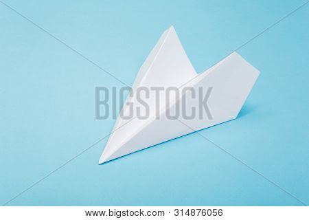 Flat Lay Of White Paper Plane And Blank Paper On Pastel Blue Color Background.