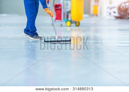 Car Mechanic Repair Service Center Cleaning Using Mops To Roll Water From The Epoxy Floor. In The Ca