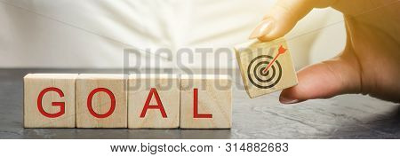 Business Woman Holds Wooden Blocks With The Word Goal. The Concept Of Achieving Business Goals. Reac