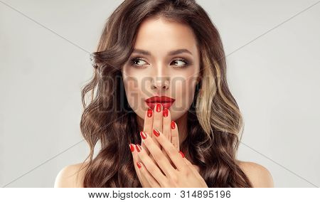 Beautiful Girl  Long , Curly Hair . Model Woman Showing A Red   Manicure On Nails   . Cosmetics And