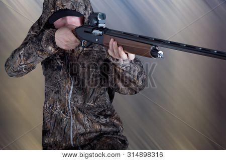 Hunter In Camouflage Clothing With A Gun On Abstract Background. The Man With The Shotgun. Young Guy