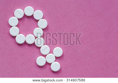 Sign Of A Woman From Pills On A Colored Background. The Concept Of Womens Health And Sexuality. Prob