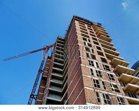 Skyscraper Construction. Сrane Near Building Under Construction. Construction Site.