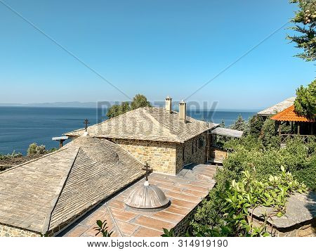Holy Mount Athos. Monastery Buildings Covered With Orange Tiles Against The Background Of The Sea