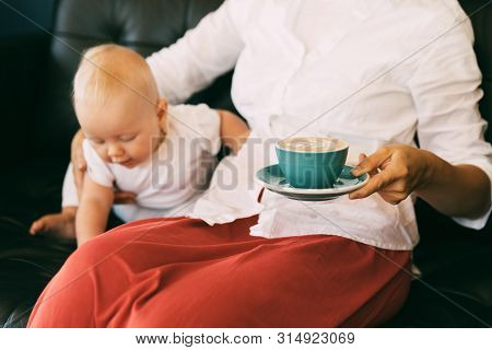 Active And Inquisitive Child Six-month-old Baby, Mom Sits Nearby And Holds A Coffee Mug With Cappucc