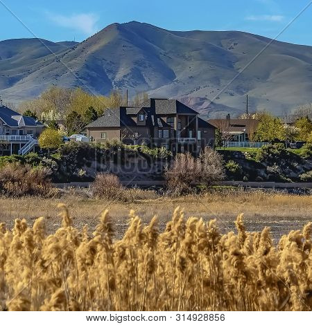 Frame Lakefront Houses With Towering Mountain And Blue Sky Background On A Sunny Day