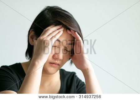 A Short Hair Caucasian Woman Close Her Eyes And Hold The Head With Two Hands; Feeling Weary And Head
