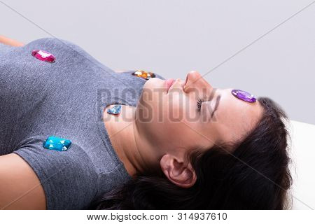 Photo Of Young Woman Undergoing Hypnotherapy With Stones