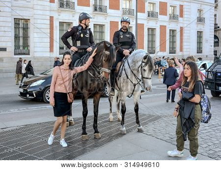 Madrid, Spain-24 February 2019: Unknown Girl Posing With Police On Horses On Square