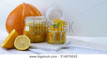 Pumpkin Jam Or Marmalade With Orange And Lemon. In The Background Is A Pumpkin. Two Glass Jars Of Pu