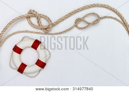 Flat Lay Of Rope With Sea Knot And Life Preserver. Summer Vacation Background. Copy Space.