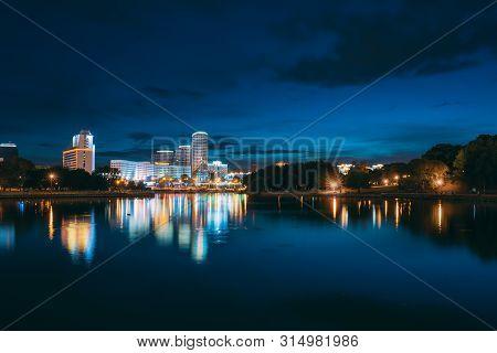 Minsk, Belarus. Pobediteley Avenue In Summer Evening, Night Lights Illumination. Svisloch River.