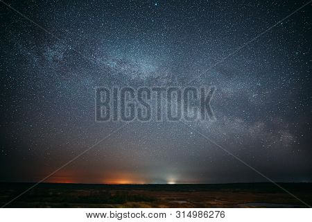 Night Starry Sky With Glowing Stars Above Forest Landscape. Dark Night Starry Sky Above Ground.