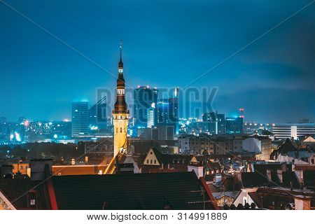 Tallinn, Estonia. Tower Of Town Hall On Background With Modern Urban Skyscrapers. Night City Centre