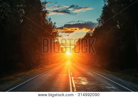 Sun Rising Over Asphalt Country Open Road In Sunny Morning Or Evening. Open Free Road In Summer Or A