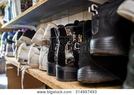Small Shoe Rack Fully Filled With Many Shoes, Sneakers And Sandals. Too Many Shoes Make The Shoe Rac