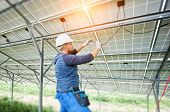 Young electrician connecting electrical cables inside the lit by sun solar modules. Installing and wiring of solar photo voltaic panel system. Alternative energy and profitable investment concept. poster
