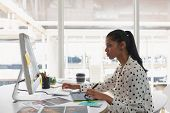 Side view of beautiful mixed-race female graphic designer using graphic tablet at desk in office. Modern casual creative business concept poster