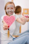 Facial dry skin and body care, complexion treatment at home concept. Happy young woman loving having grey mud mask on her face, holding sponge in heart shape. poster