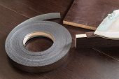 Roll melamine edge for finishing of furniture and smoothing-iron used for gluing edges. Edging tape on laminated chipboard sheets wenge color. poster
