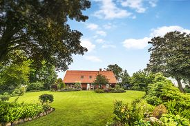 Red Brick House In A Beautiful Garden In The Summer With A Green Lawn Under A Blue Sky