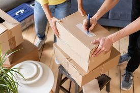 Close Up Of Hand Packing Cardboard Box, Concept Moving House. Young Couple Moving To A New Apartment