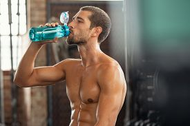 Sweaty young man at gym drinking water after intensive workout session at gym. Athletic shirtless guy drinking from water bottle while resting. Muscular thirsty man sweating after strength training.
