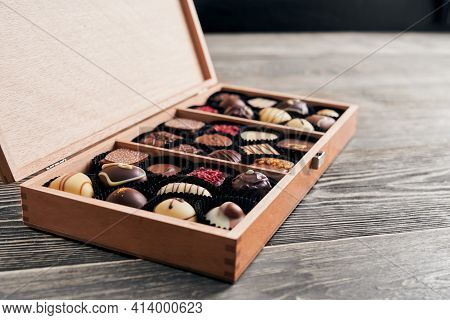 Assortment Of Chocolate Handmade Candies In Opened Wooden Box. Romantic And Tasty Present For Holida