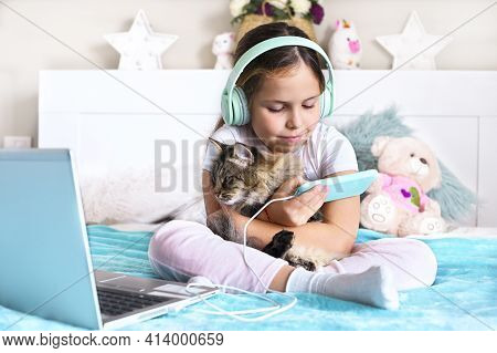 Child With Headphones Playing A Computer Game On The Phone. A Little Girl Lies On The Bed And Fluffy