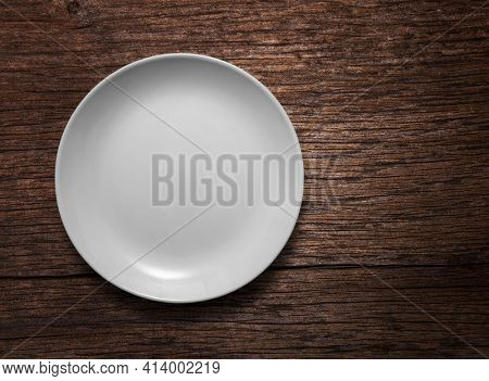 Blank white ceramic round dish on wooden desk background with copy space